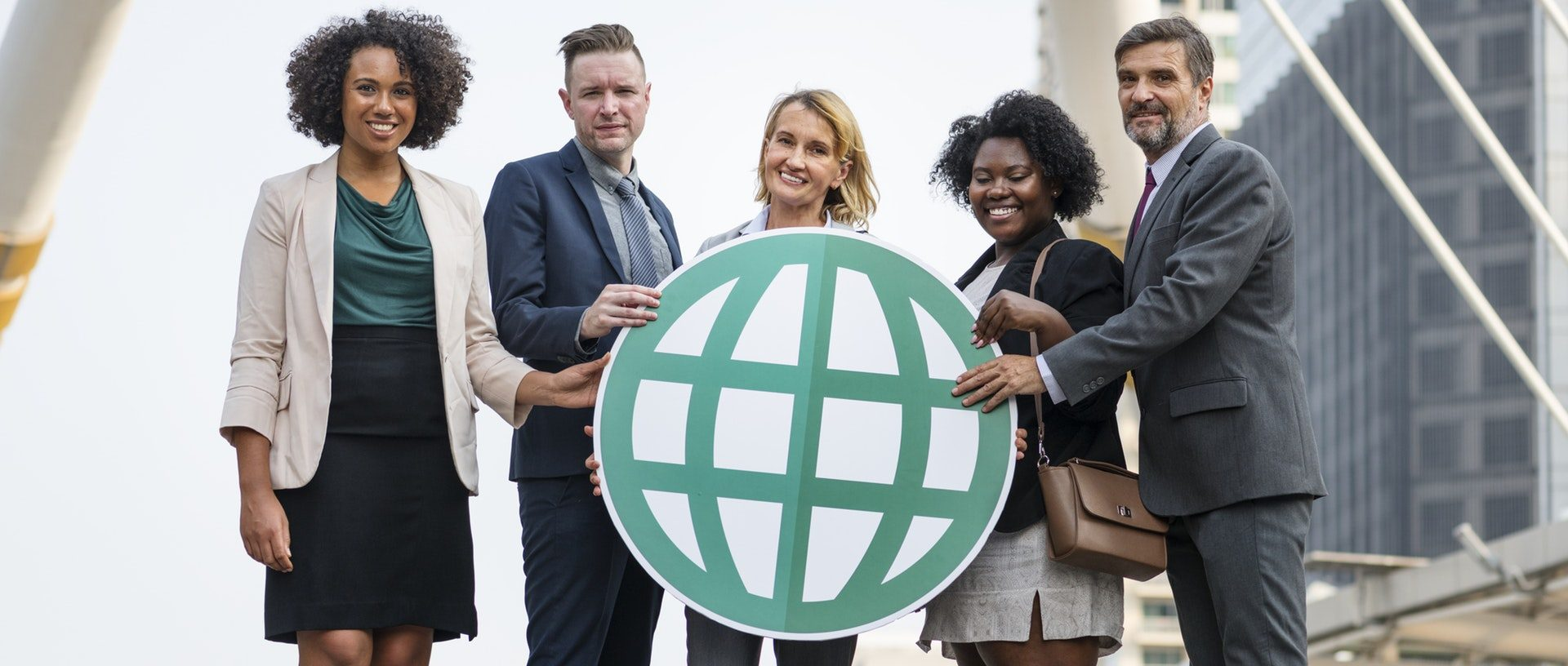 five business people travelling for business holding a paper world